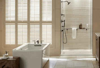 A beautiful modern bathroom with sun shining in through adjustable blinds. This great space may have been the result of a full remodel or tub and shower replacement.