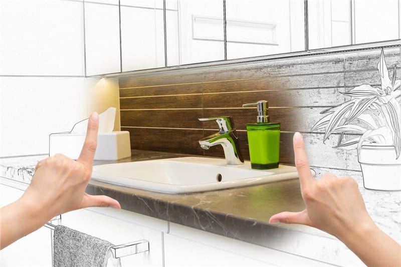 A homeowner envisions a bathroom remodel. Part of the picture is a photograph and the rest is a concept sketch. Remodeling a bathroom on a budget will be easy with our handy guide.