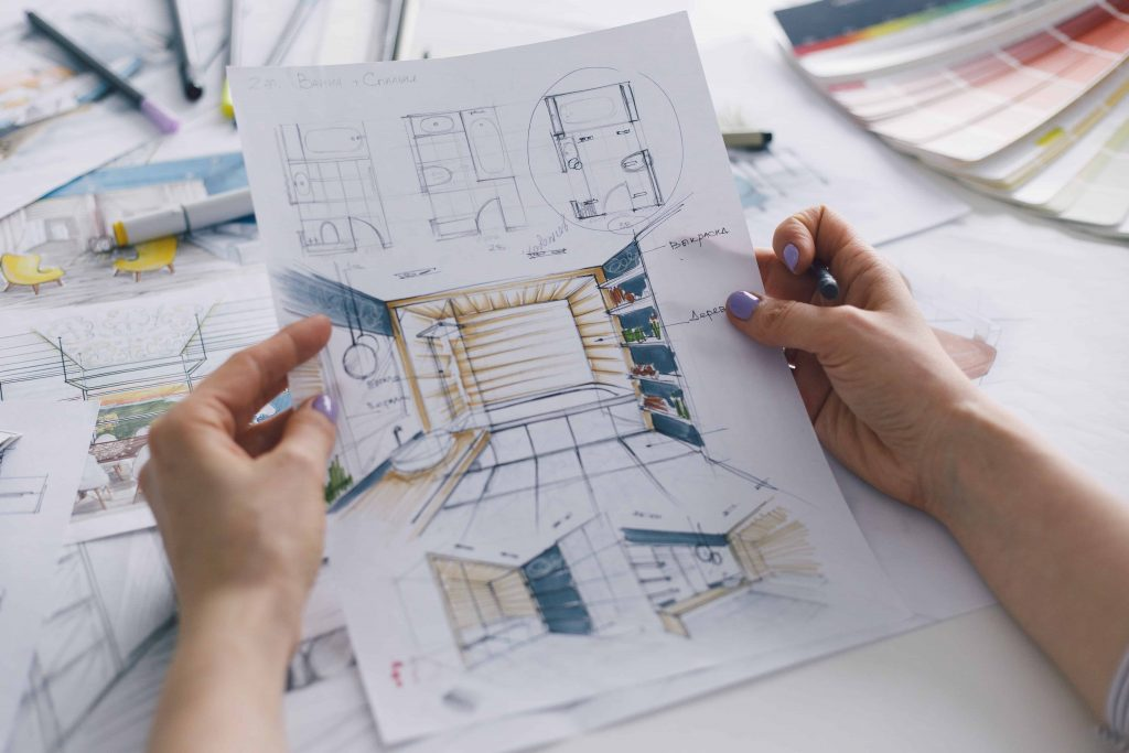 A homeowner looks over plans while she considers reasons to remodel a bathroom.