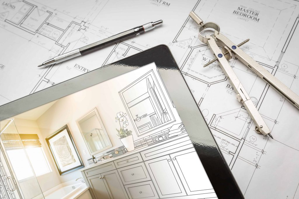 Computer tablet with master bathroom design over house plans, pencil and compass. Careful planning is part of avoiding bathroom remodeling mistakes.