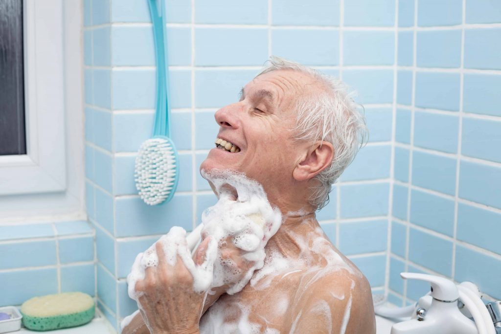 A senior man bathes. Resolving the question of walk in tubs vs showers can be a crucial step to maintaining seniors' independence.